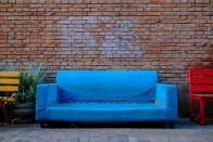 A blue couch between a yellow and a red bench.